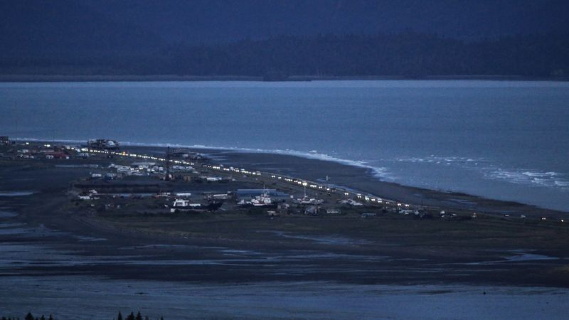 Headlights from a line of cars shine at dusk on the Spit in Homer, Alaska. (Pat Williams...