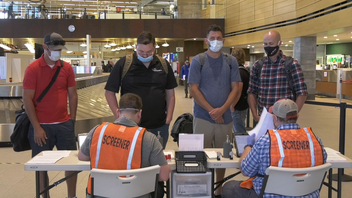 Screeners at Fairbanks International Airport talk to passengers on a flight from Seattle to...