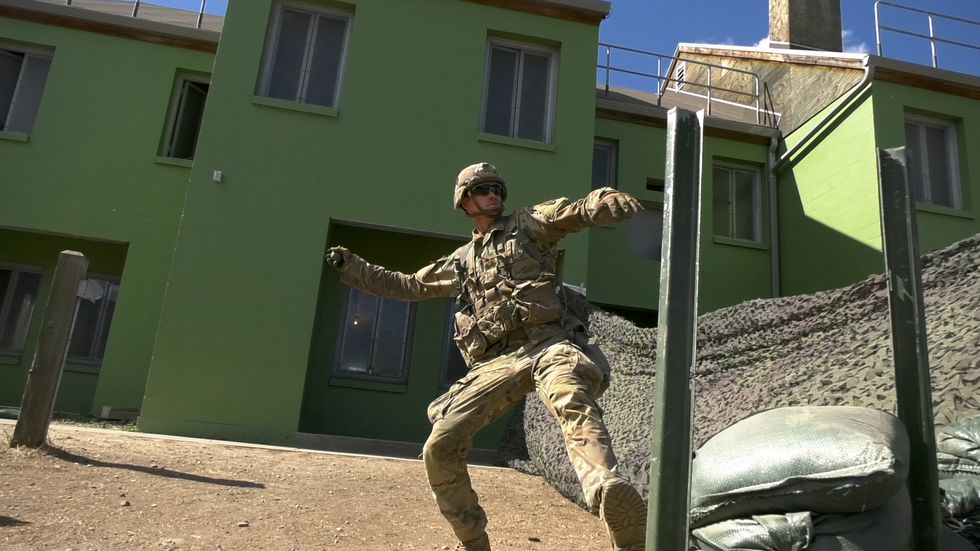 A soldier practices throwing a hand grenade before his test. They are required to be able to...