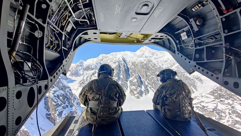 Two soldiers from Fort Wainwright sit on the ramp of a Chinook as they return from unloading...