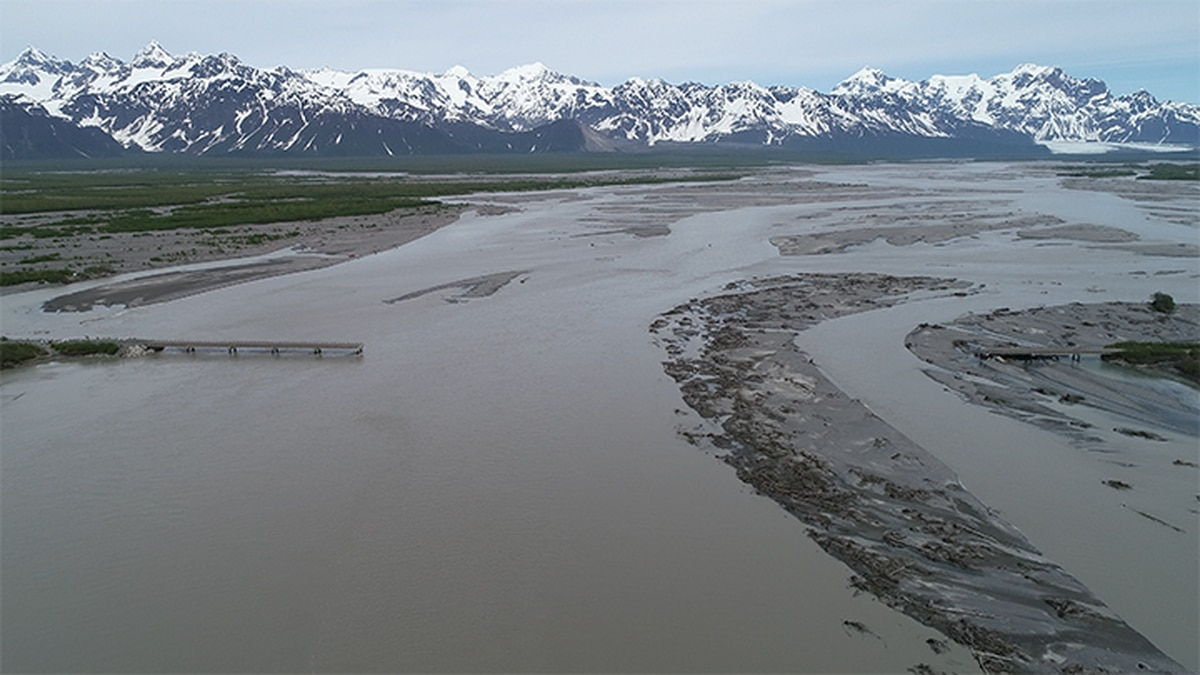 The Copper River washed away a piece of land connecting two bridges on the highway. Those...