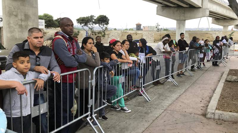 In this Sept. 26, 2019 file photo, asylum seekers, in Tijuana, Mexico, listen to names being...