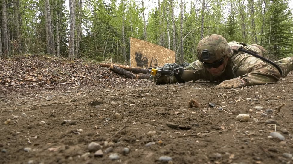 PV2 Hunter Cameron, an infantryman with 11B at Fort Wainwright practices his low crawl as he...
