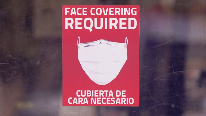 A mask required sign is displayed on the entrance to a business Tuesday, March 2, 2021, in...