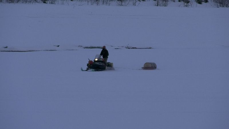 An individual is seen riding a snowmachine near the Tanana River boat launch in Fairbanks....