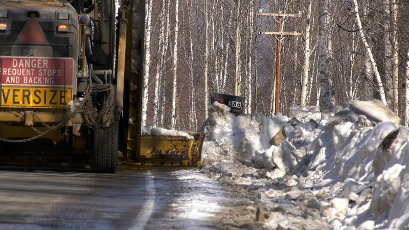A DOT grader wings a road in Fairbanks. Winging is when operators push the snow over the edge...