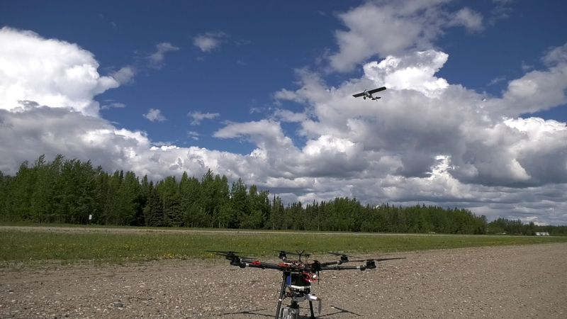 A manned aircraft flies above an ACUASI drone. ACUASI is conducting testing to see if a drone...