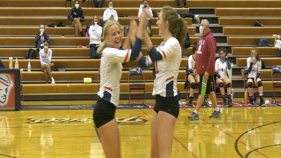 Kinley Erickson and Ainsley Smith celebrate after scoring a point against the Grace Christian...