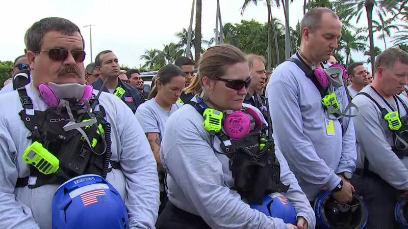 During a moment of silence Wednesday, rescue workers stood at solemn attention and clergy...