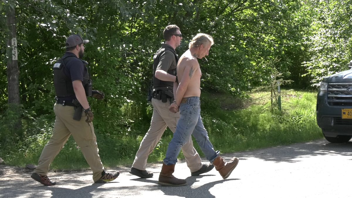 Adult Probation officers take a suspect into custody after Alaska State Troopers helped serve a warrant for the individual. (Sara Tewskbury/KTVF)
