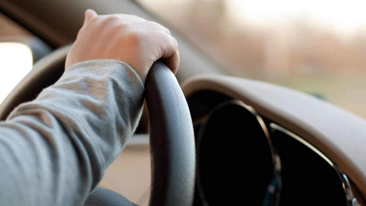 A woman drives a car with one hand. The Alaska Department of Administration had proposed...