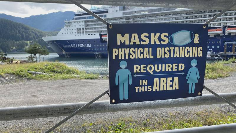 A sign reminds people that masks and social distancing is required at the Holland America...