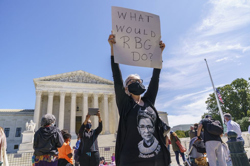 Kelli Midgley, center, an English teacher from Baltimore,  joins people gathered at the Supreme Court to honor the late Justice Ruth Bader Ginsburg, in Washington, Saturday, Sept. 19, 2020.