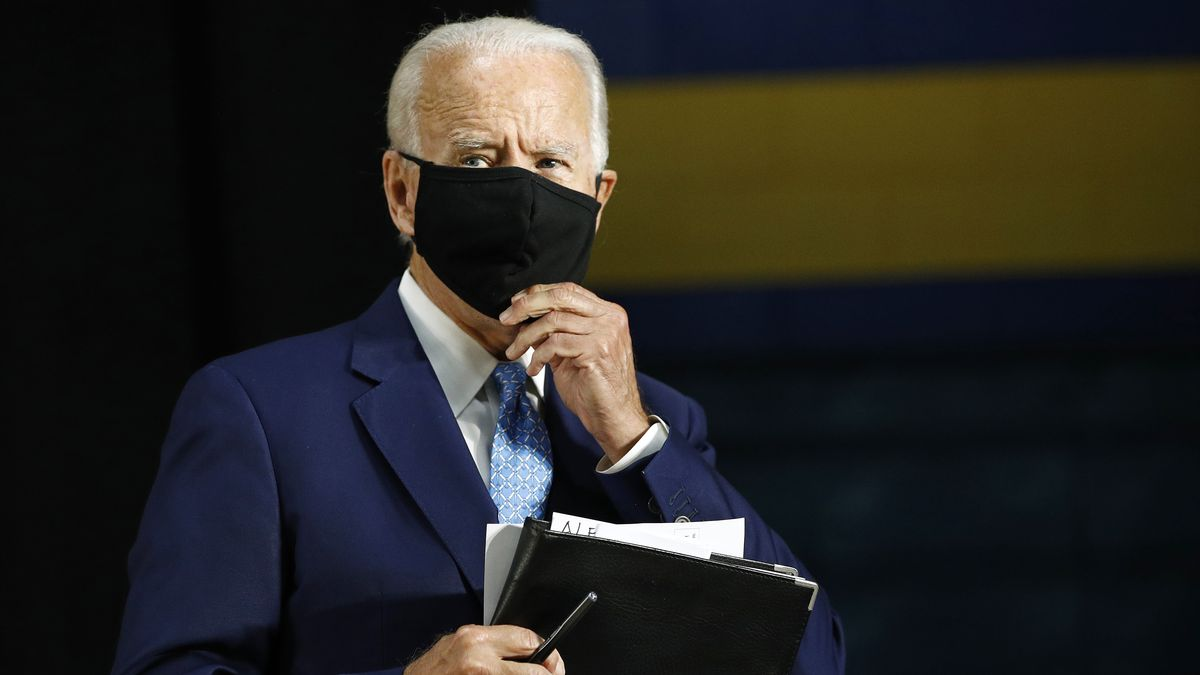 Former Vice President Joe Biden puts on a face mask to protect against the spread of the new coronavirus as he departs after speaking at Alexis Dupont High School in Wilmington, Del., Tuesday, June 30, 2020.