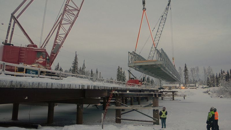 Two cranes work in tandem to install a section of a temporary pedestrian bridge over the Chena...