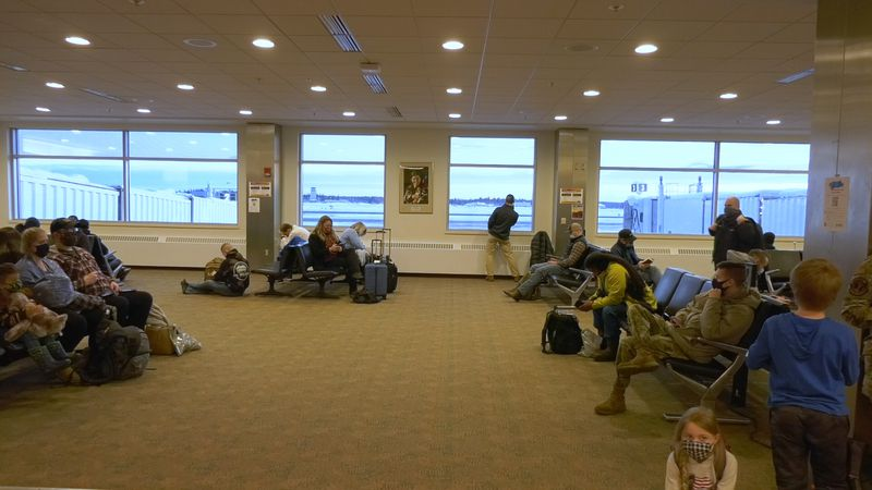 Travelers wait in the Fairbanks International Airport for a flight to Seattle. While some...