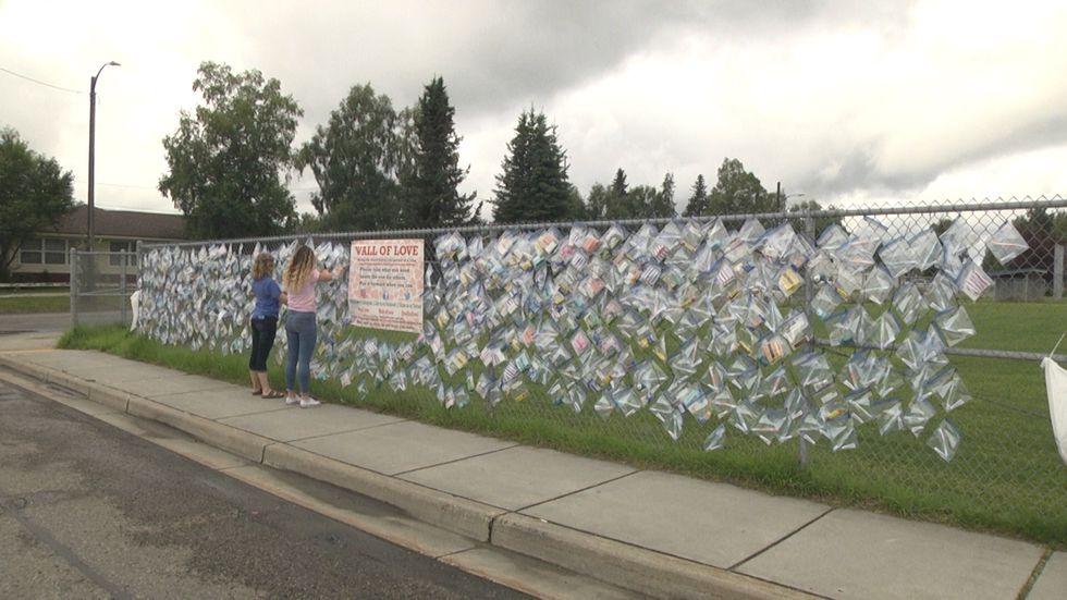 Teagan Gutka and Hailey Baker hang items near Denali Elementary School Saturday morning.