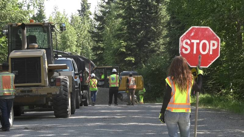 A flagger stops cars on Rosie Creek Road as crews work to install culverts on the road.
