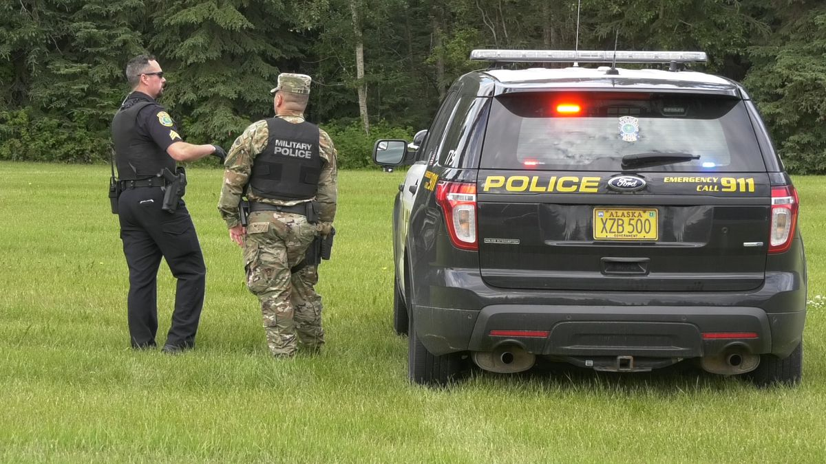 Police surrounded a wooded area near Fort Wainwright after two suspects ran into the woods...