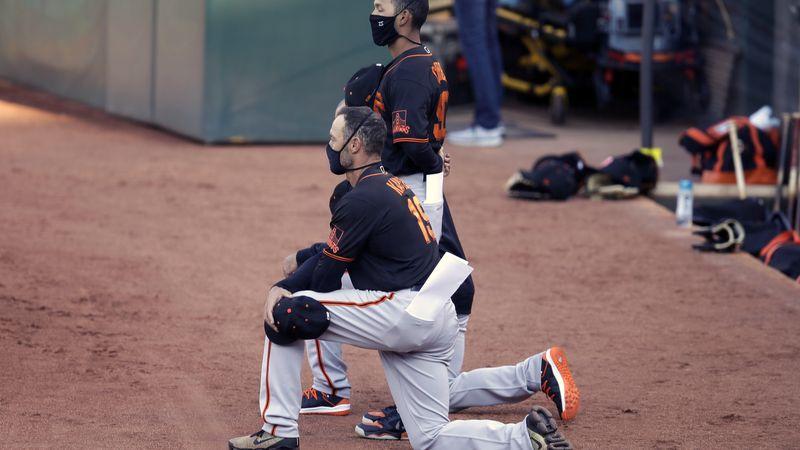 San Francisco Giants' manager Gabe Kapler kneels during the national anthem prior to an...