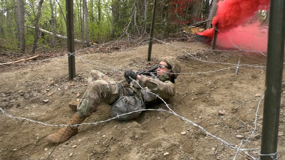 First Lieutenant Emily Raab crawls under barbed wire during one of the Expert Field Medical...
