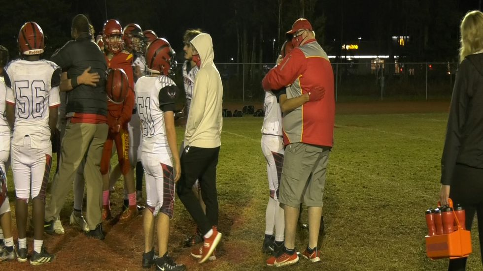 West Valley Head Coach David DeVaughn hugs it out with some of his former players who play on Eielson.