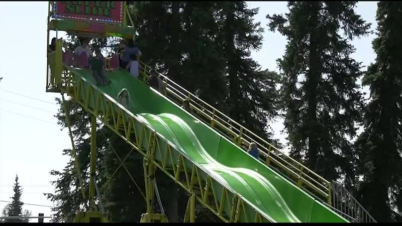 Children going down a slide at the Tanana Valley State Fair.