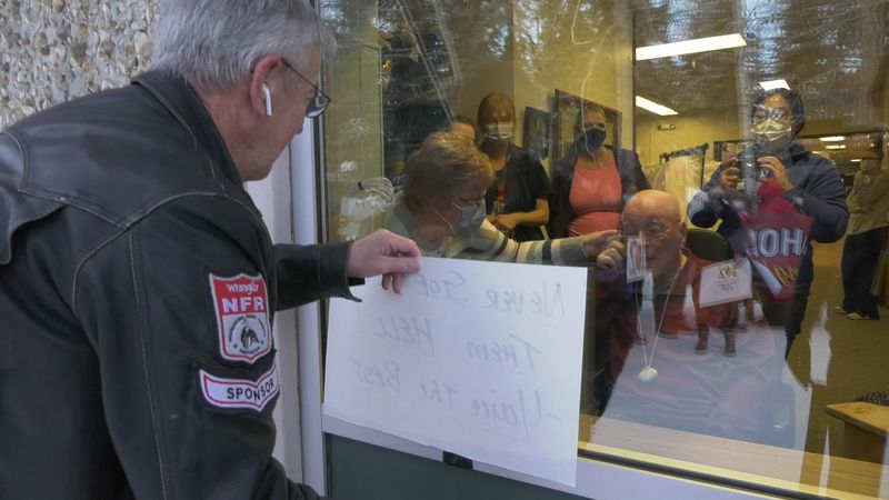 Ralph Seekins wishes 102 year old Urban Rahoi a happy birthday from outside the window off the...