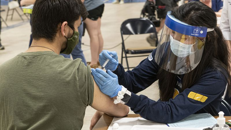 Kent State University student Jarrett Woo gets his Johnson & Johnson COVID-19 vaccination from...