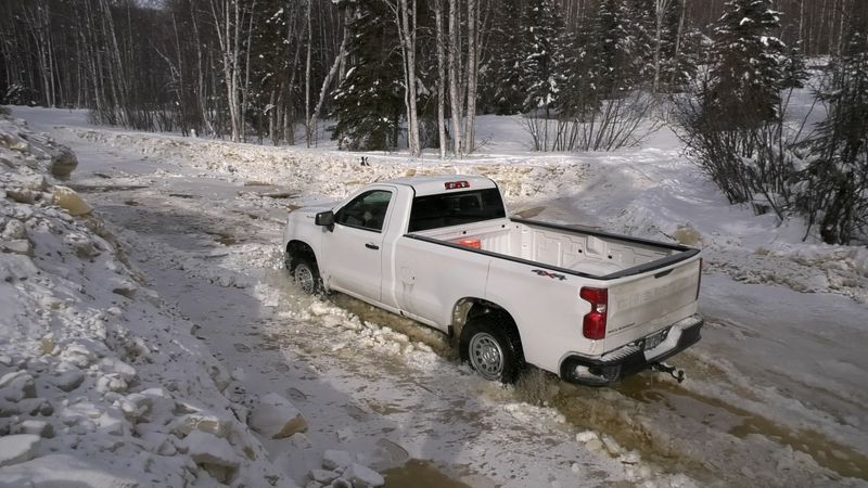 Tim Manning attempts to drive his truck through a flooded and frozen section of road off of...