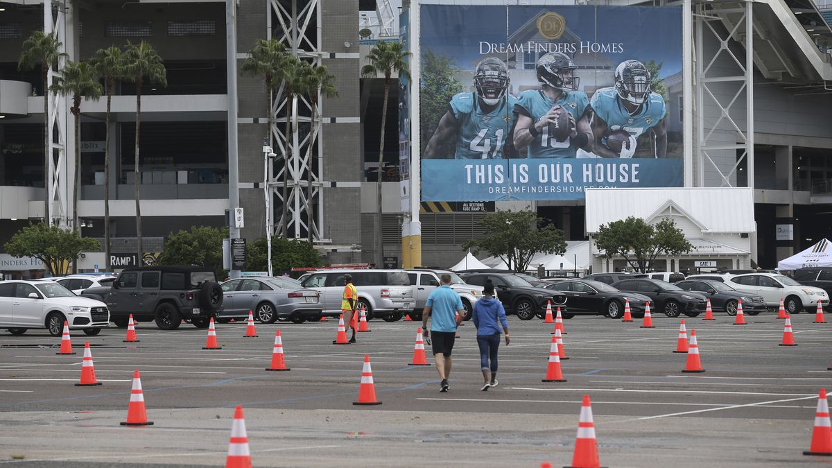 FILE - In this Sept. 13, 2020 file photo, fans walk through a parking lot with cones to social...