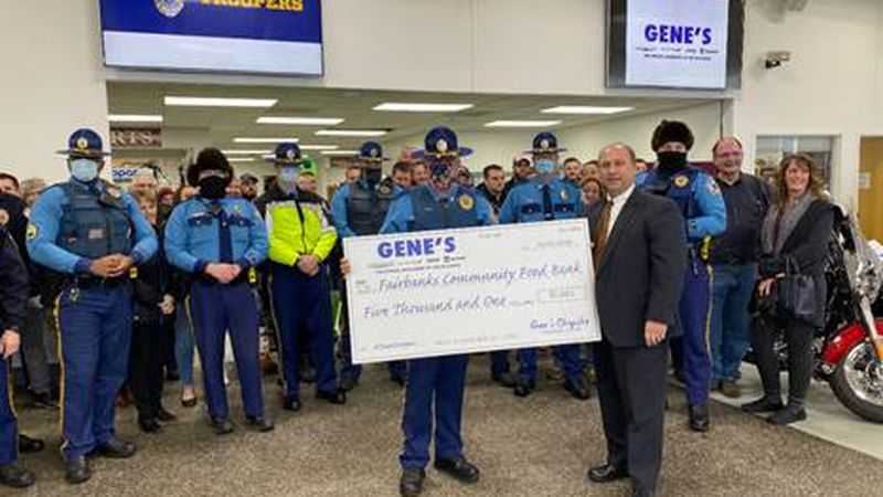Captain Ron Wall, Commander Alaska State Troopers D Detachment, accepts a donation for the...