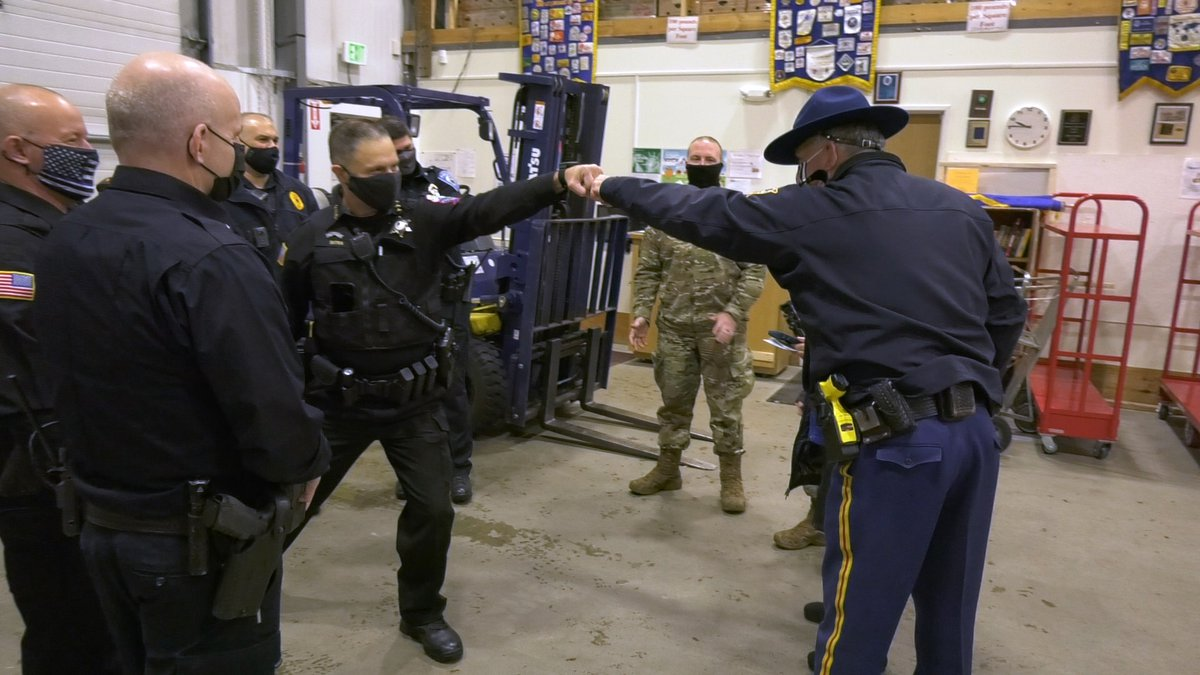 Captain Ron Wall of the Alaska State Troopers and Chief Steve Dutra fist bump after they broke...