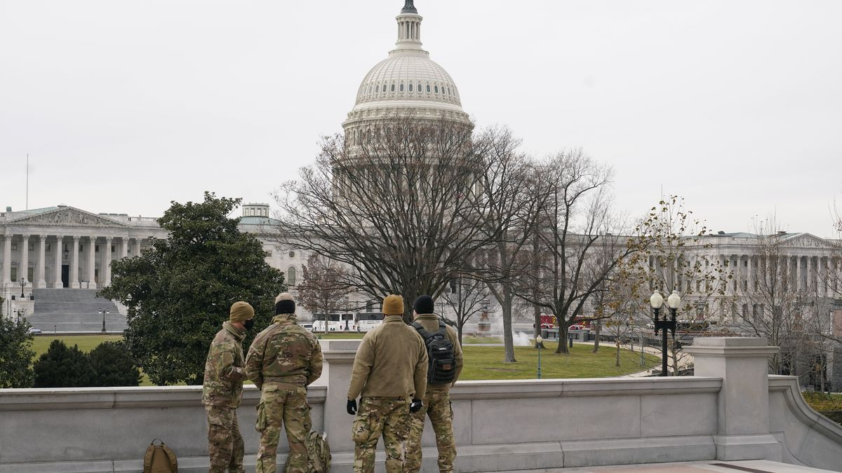 With the U.S. Capitol Building in view, members of the military stand on the steps of the...