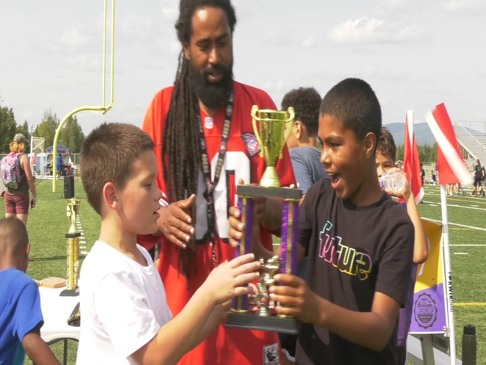 Players celebrate with the championship trophy at the 7v7 Tournament.