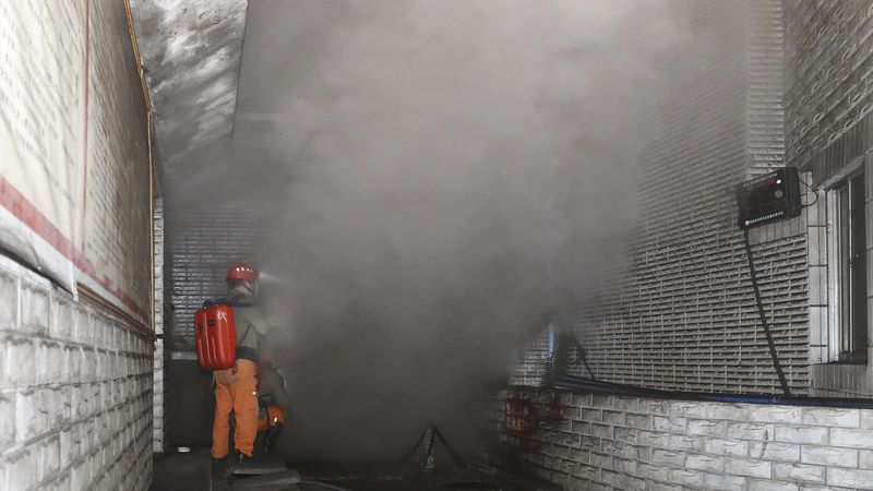 In this photo released by Xinhua News Agency, rescue workers gauge the density of carbon...