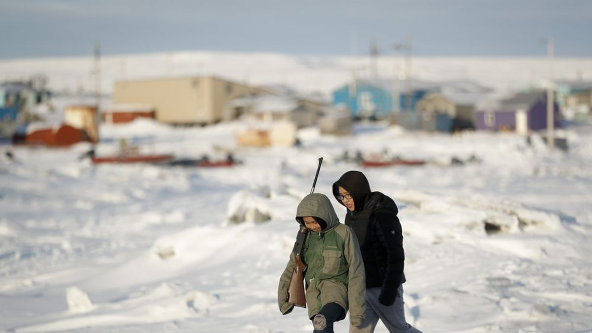 FILE - In this Jan. 18, 2020, file photo, George Chakuchin, left, and Mick Chakuchin walk on ice over the Bering Sea in Toksook Bay, Alaska, a mostly Yuip'ik village. A federal judge has ruled that Alaska Native corporations are eligible for a share of coronavirus relief funding set aside for tribes. Congress included $8 million for tribes in a relief package approved earlier this year. (AP Photo/Gregory Bull, File)