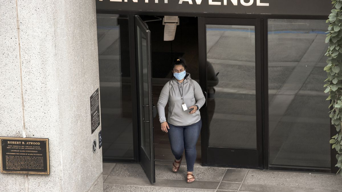 A woman wearing a face mask exits the Atwood Building, a downtown Anchorage, Alaska, building...