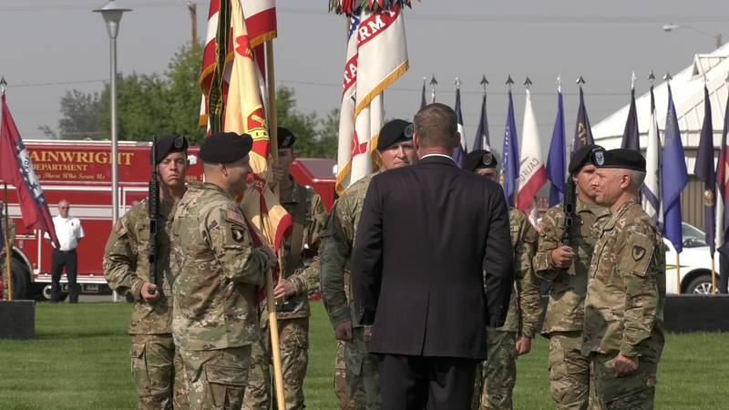 Colonel Chris Ruga passes the organization colors to Colonel Nate Surrey in a change of command...