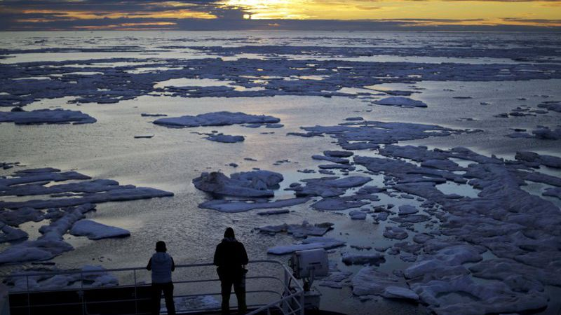 File Photo: Researchers look out from the Finnish icebreaker MSV Nordica as the sun sets over...