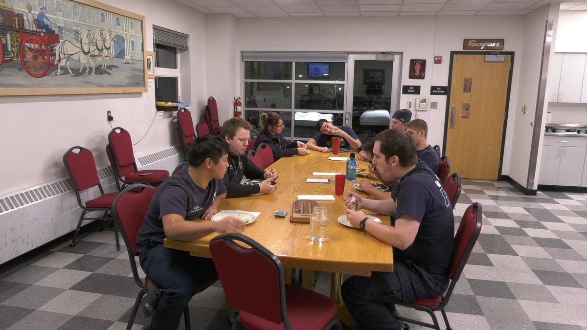 Members of the Fairbanks Fire Department sit down to enjoy a meal of homemade street tacos. (John Dougheryt/KTVF)
