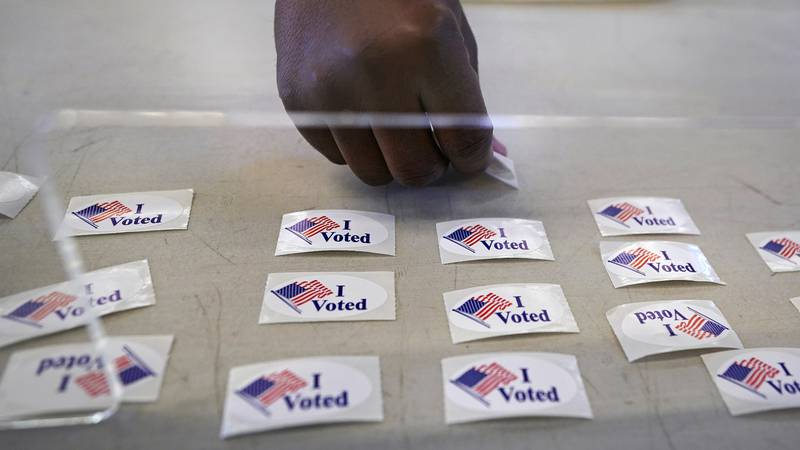 """A voter selects an """"I Voted"""" sticker after submitting their ballot at an early voting location,..."""