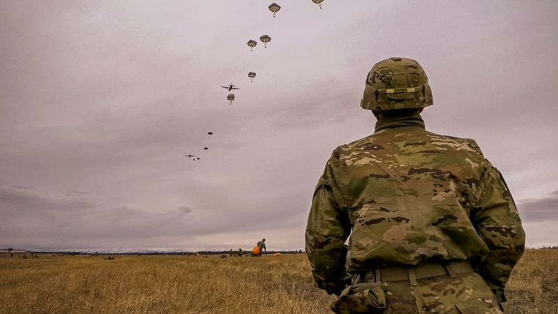 A US Army Alaska soldier watches as fellow soldiers parachute out of aircraft during a...